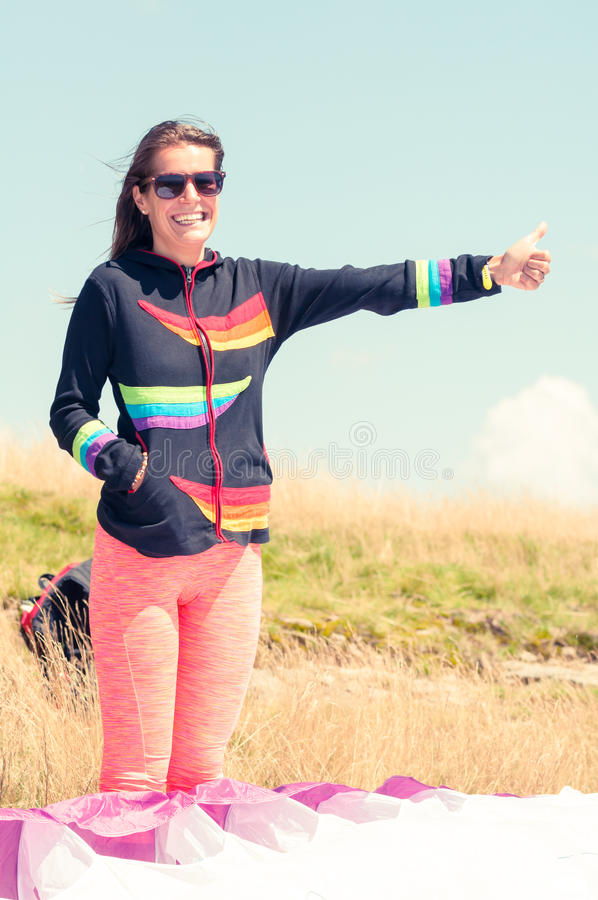 Happy girl making hitchhiking gesture for paragliding. On a summer sunny day royalty free stock images