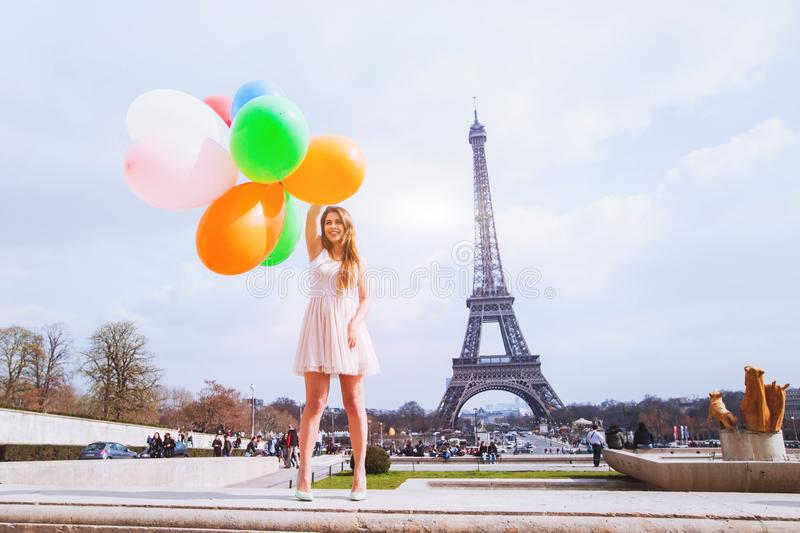 Happy girl with multicolored balloons near Eiffel tower in Paris stock image