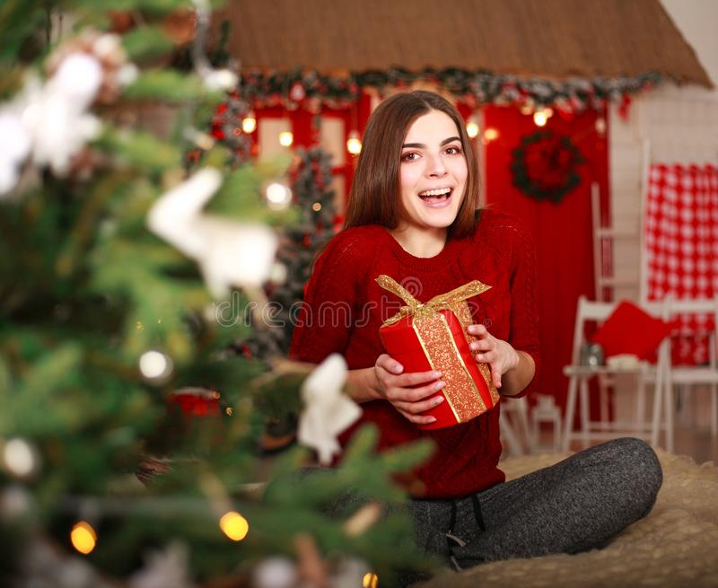 Happy girl opens gift in holiday at home on Christmas Eve. Happy smiling girl opens a gift in a holiday at home on Christmas Eve stock photos