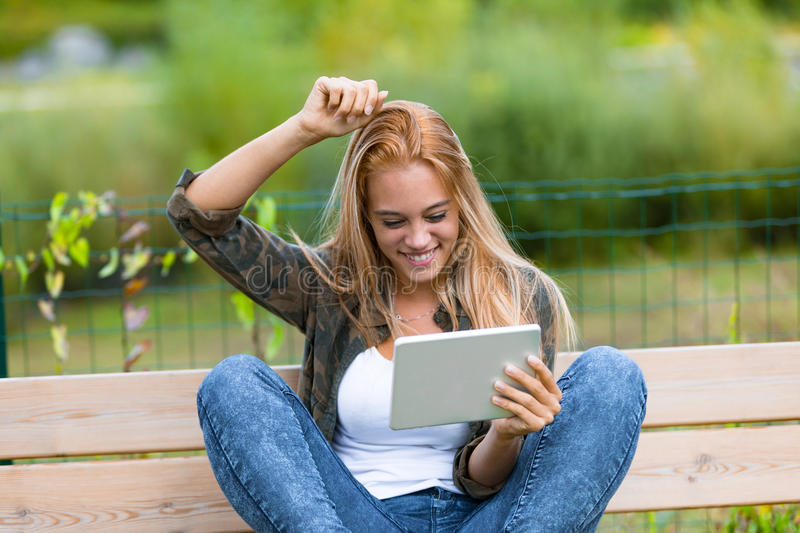 Happy girl outdoors with a tablet. Girl rising er harm because she`s successful or winning or simply to scratch her head, she`s reading something on her digital royalty free stock images