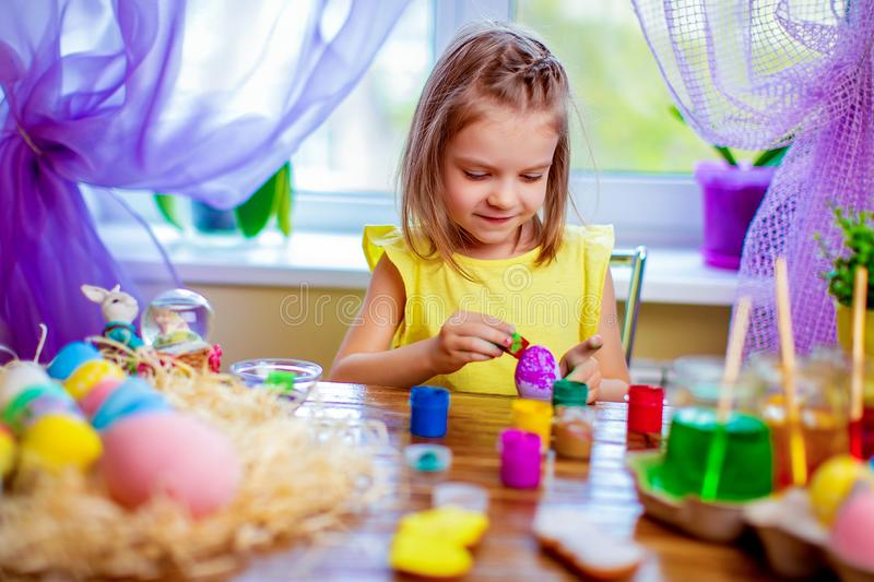 Happy girl painting easter eggs, small child at home have fun. spring holiday. Colorful painted eggs, flowers in vase. Happy easter girl having fun and painting stock images