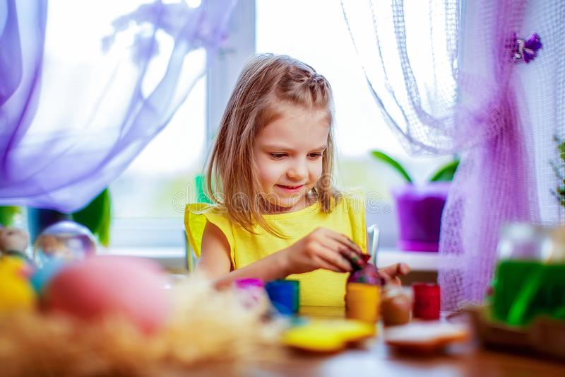 Happy girl painting easter eggs, small child at home have fun. spring holiday. Colorful painted eggs, flowers in vase. Happy easter girl having fun and painting stock photos