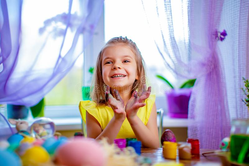 Happy girl painting easter eggs, small child at home have fun. spring holiday. Colorful painted eggs, flowers in vase. Happy easter girl having fun and painting royalty free stock photos