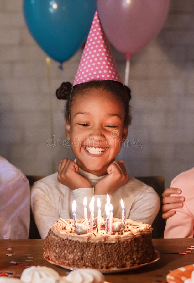 Happy girl in party hat with birthday cake stock photos
