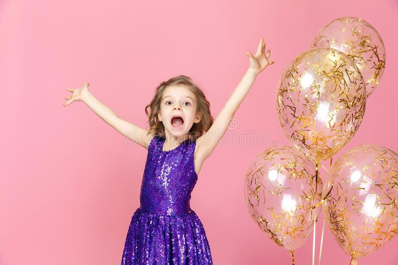 Happy girl in pink dress celebrating stock images