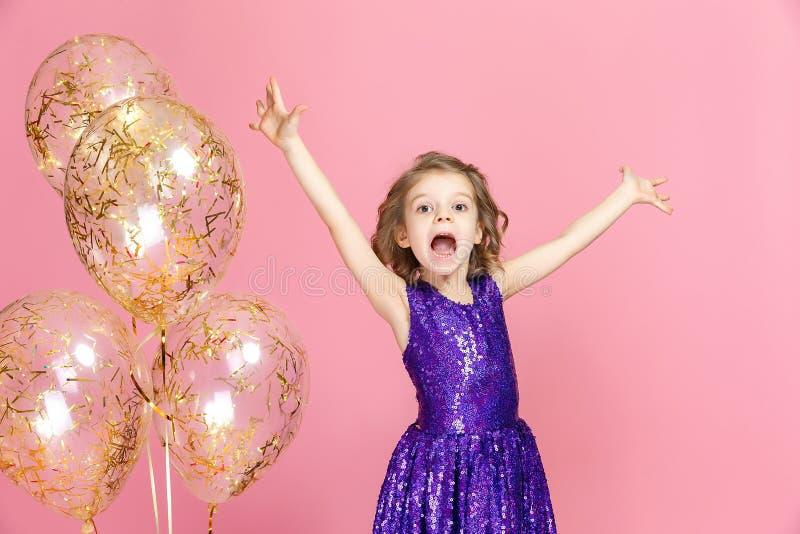 Happy girl in pink dress celebrating stock image