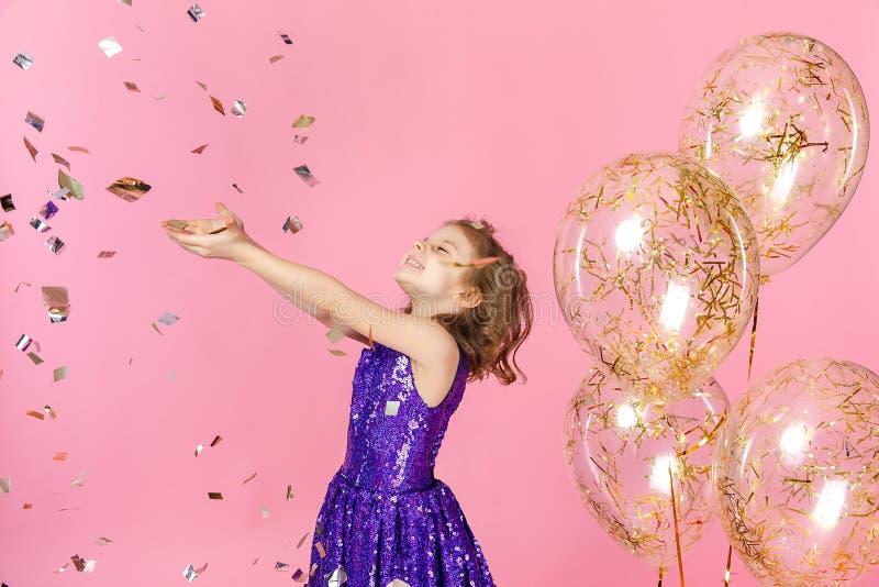 Happy girl in pink dress celebrating stock photo