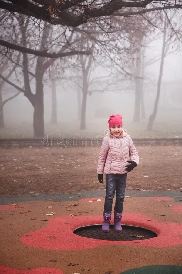 Happy girl in a pink jacket jumping on the trampoline outdoors in park. Autumn, misty forest. royalty free stock photos