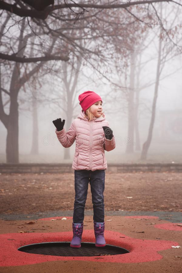 Happy girl in a pink jacket jumping on the trampoline outdoors in park. Autumn, misty forest. royalty free stock photo