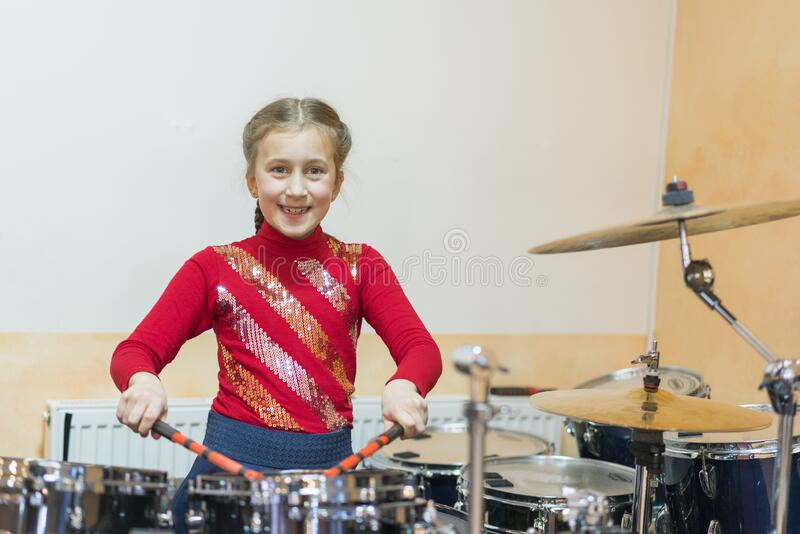 Happy girl playing the drums. Teen girls are having fun playing drum sets in music class. Girl in red drumming royalty free stock images