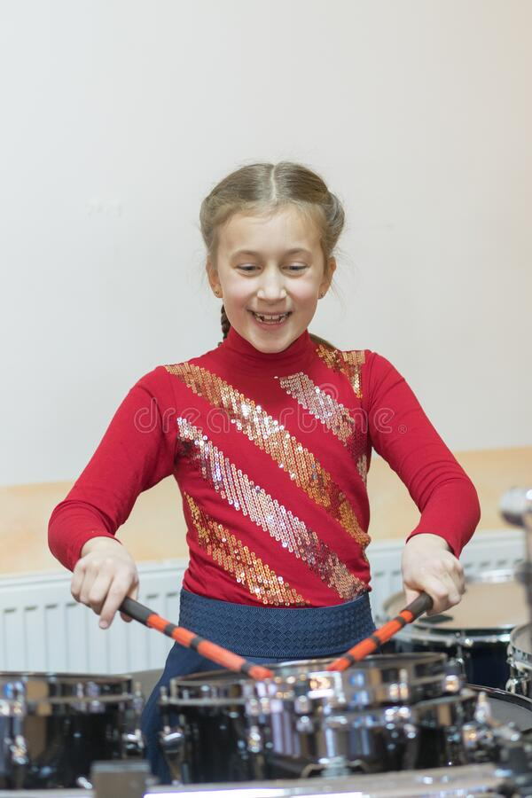 Happy girl playing the drums. Teen girls are having fun playing drum sets in music class. Girl in red drumming. vertical photo stock image