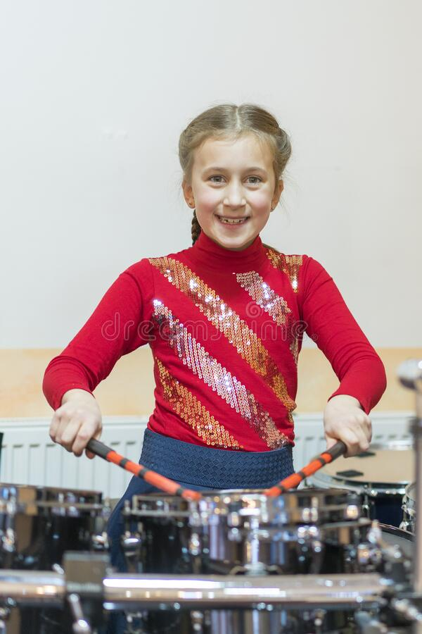 Happy girl playing the drums. Teen girls are having fun playing drum sets in music class. Girl in red drumming. vertical photo royalty free stock photos