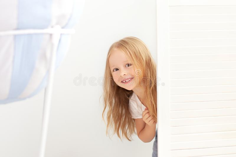 Happy girl playing hide and seek in wardrobe. Active child looking hiding behind a white door. A child with a happy face, playing stock image