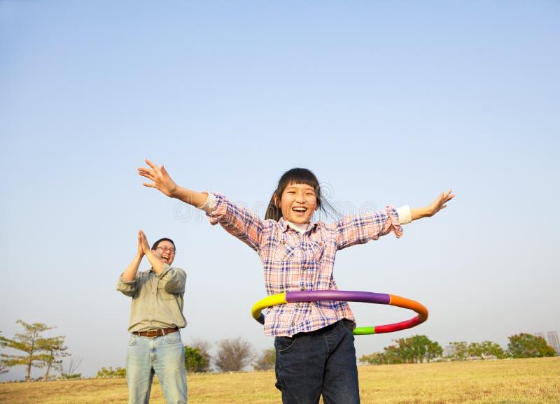 Happy girl playing hula hoops. Happy kid playing hula hoops outdoors royalty free stock image