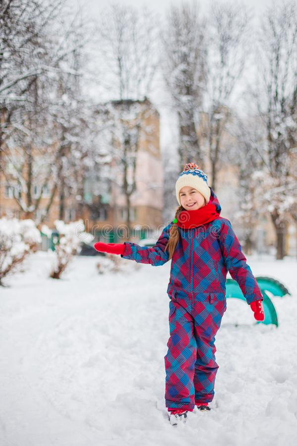 Happy girl playing with snow on a snowy winter walk, making snowballs in the park royalty free stock photography
