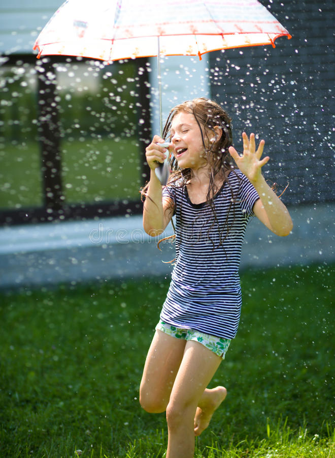 Happy girl is playing under rain. On backyard stock photography