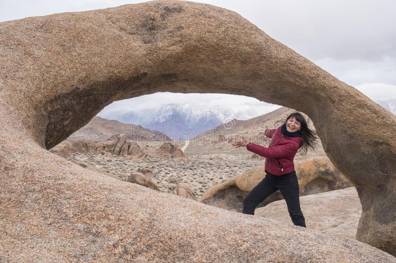 Happy girl pointing to an arch in the beautiful formations of Alabama Hills stock images