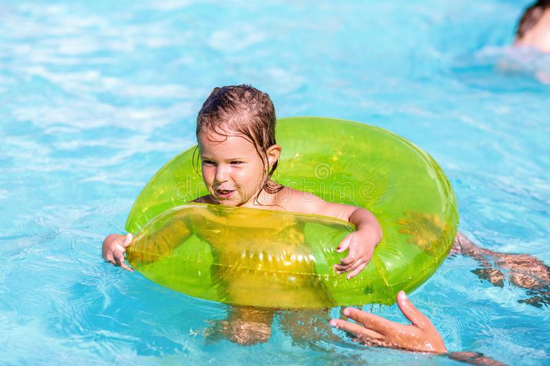 Happy little girl in a pool in at green life preserver learning to swim stock image