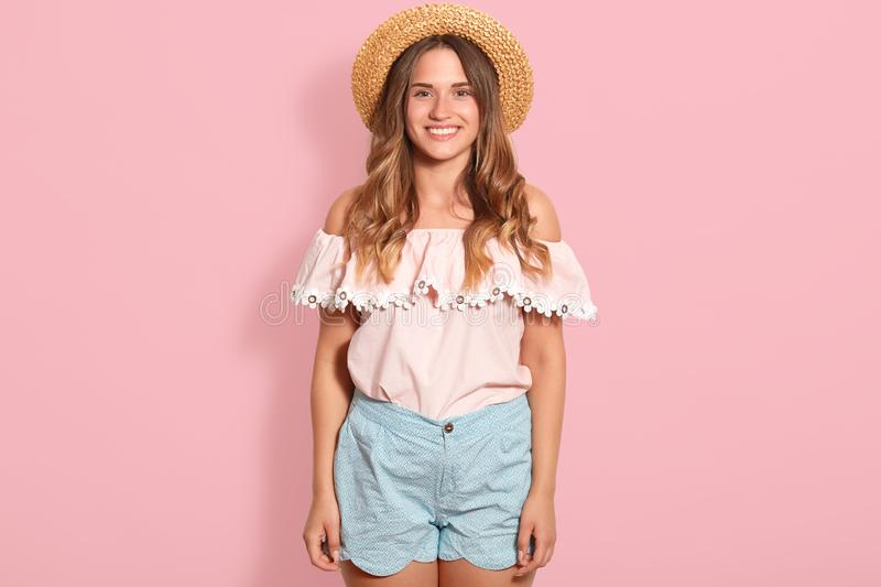 Happy girl posing in straw hat, rose summer blouse and blue short. Beautiful woman has charming smile, being in good mood,. Expresses happyness, looking royalty free stock images