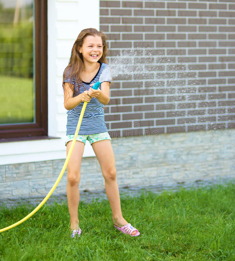 Happy girl pouring water from a hose. On backyard stock photography