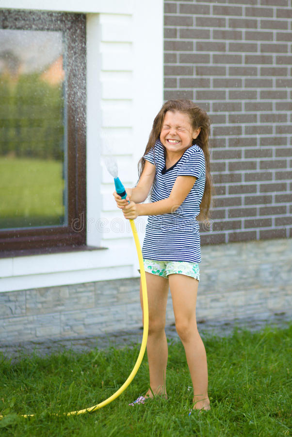 Happy girl pouring water from a hose. On backyard stock photo