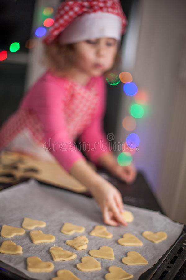 Happy girl preparing biscuits in the kitchen, casual lifestyle photo in real life interior, christmas cookies,kid in chef dress stock photo