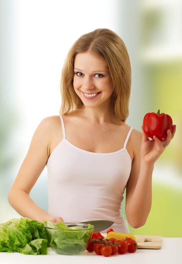Happy girl preparing vegetarian food in kitchen stock photos