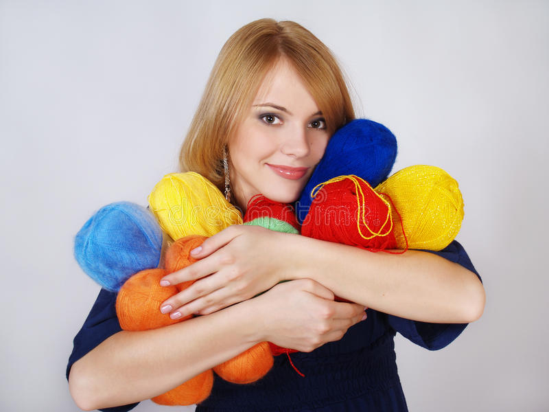 Happy girl presses a warm color yarn to the face stock images
