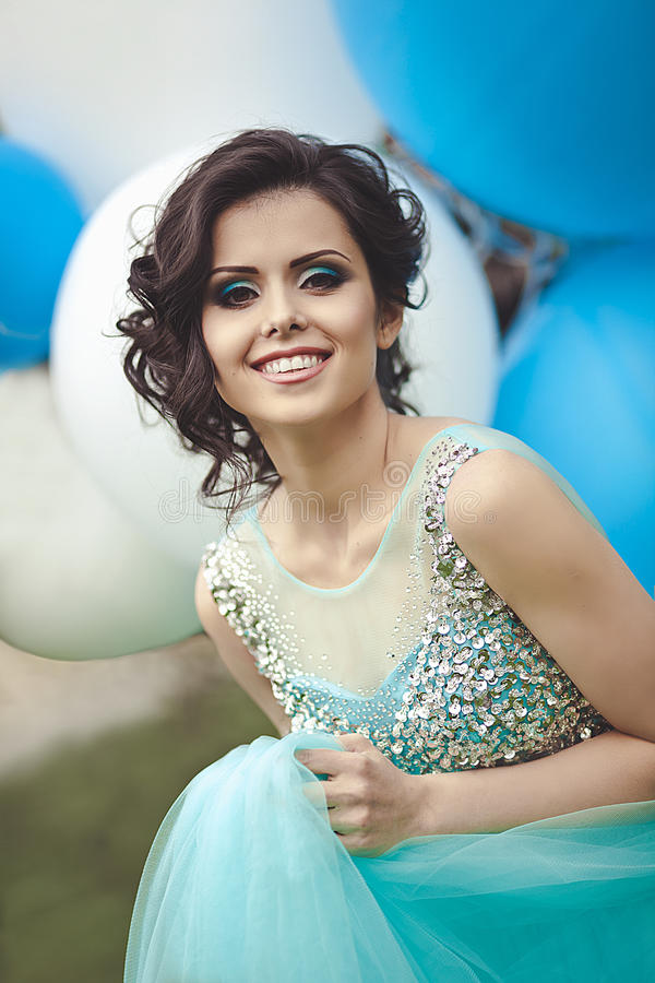 Happy girl in prom with helium air balloons. Portrait of a beautiful girl graduate in a blue dress. stock images