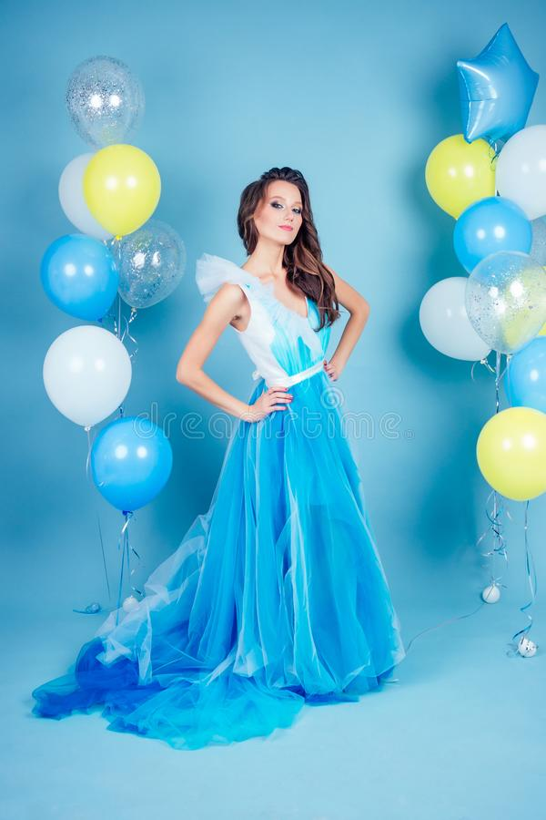 Happy girl in prom with helium air white, blue and yellow balloons. Portrait of a beautiful woman in a blue dress with a royalty free stock photography