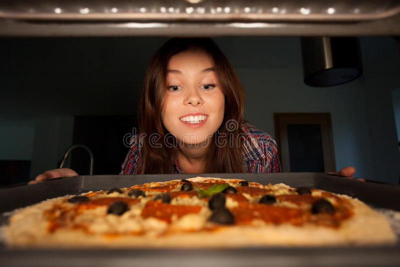 Happy girl putting pizza into oven stock photography