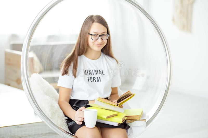 Happy girl reads an interesting book with glasses. Drinking cappuccino. Concept of education, hobby and study and world book day stock photo