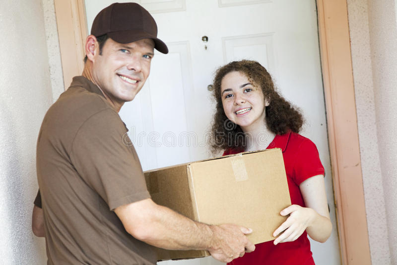 Happy Girl Receives Package. Happy customer receiving a package from a delivery man. Focus on girl royalty free stock photos