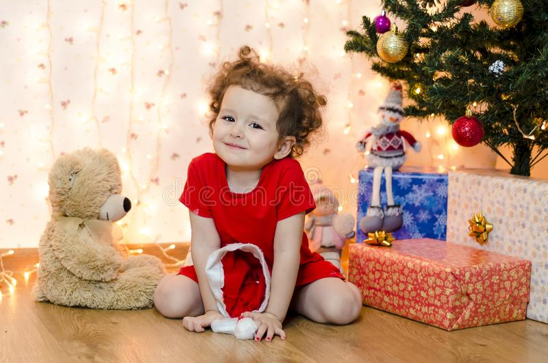 Happy girl in red festive clothes with hat under the Christmas tree waits 12 hours and presents from Santa Claus. royalty free stock photo