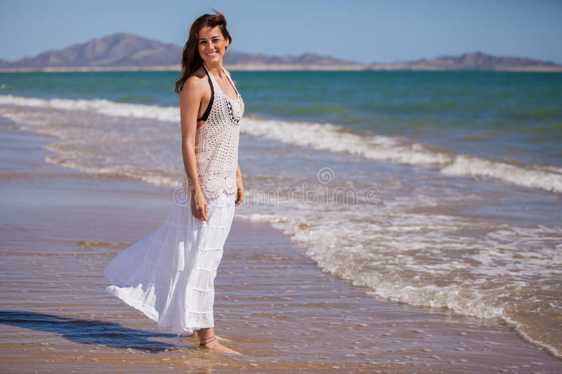 Happy girl relaxing at the beach. Beautiful Hispanic brunette walking on the beach on a sunny day stock photo