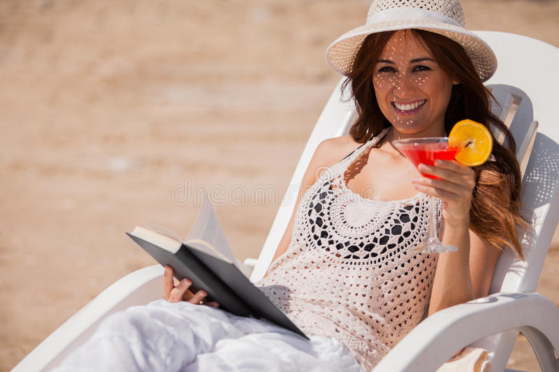 Happy girl relaxing at the beach. Beautiful Latin brunette drinking cocktails and reading a book at the beach royalty free stock photography