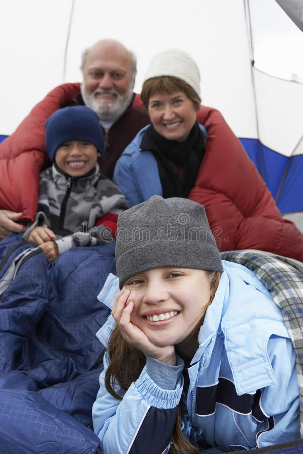 Happy Girl Relaxing With Family In Tent. Portrait of happy girl relaxing with family in tent while camping royalty free stock photos