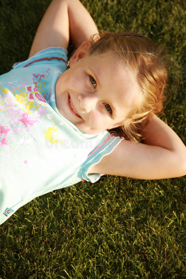 Happy girl relaxing on a grass stock image