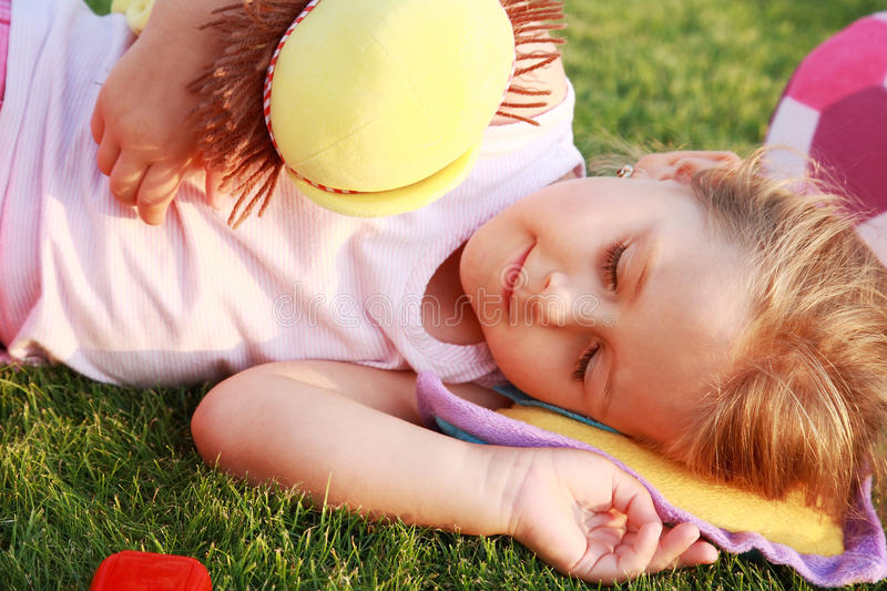 Happy girl relaxing on a grass. Happy cute girl relaxing on a grass field stock photos