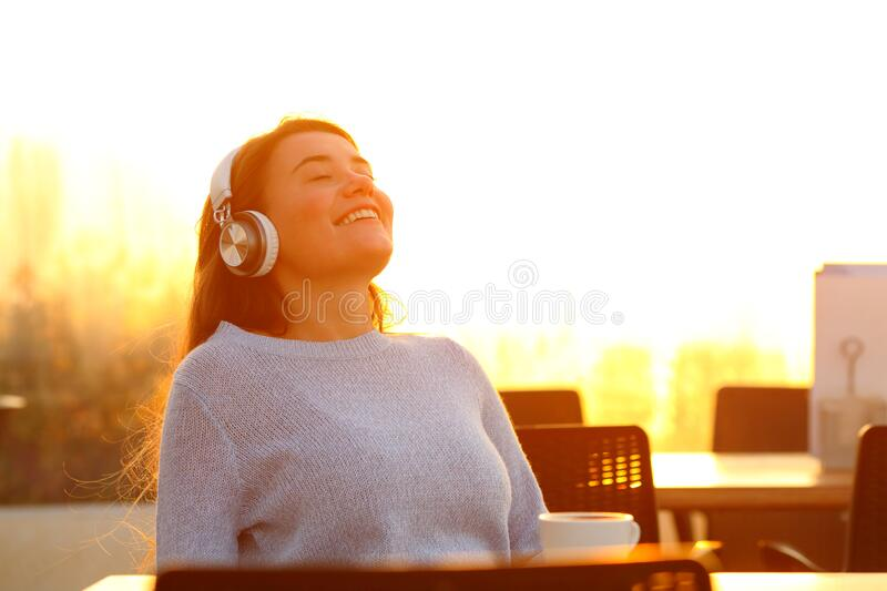 Happy girl relaxing listening to music in a terrace at sunset stock photography