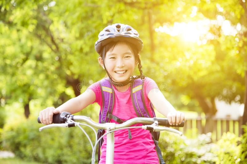Happy girl riding bicycle in the park stock photo