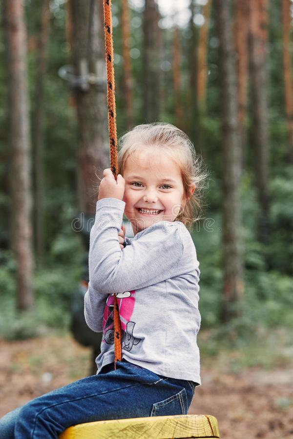 Happy girl riding on the zip line in rope park stock images