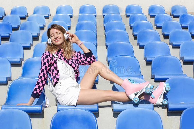 Happy girl with roller skates sitting on grandstand. Happy girl with retro roller skates sitting on grandstand royalty free stock photo
