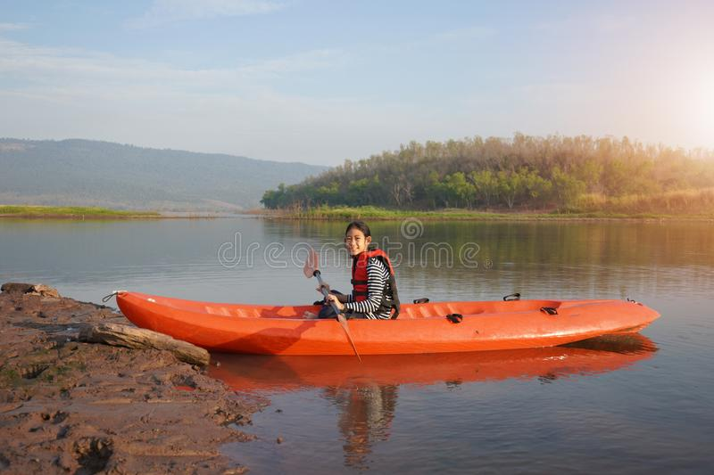 Girl rowing a canoe on calm waters royalty free stock images