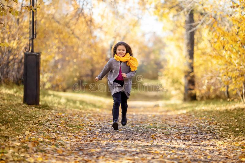 Happy girl is running in autumn park. royalty free stock photography