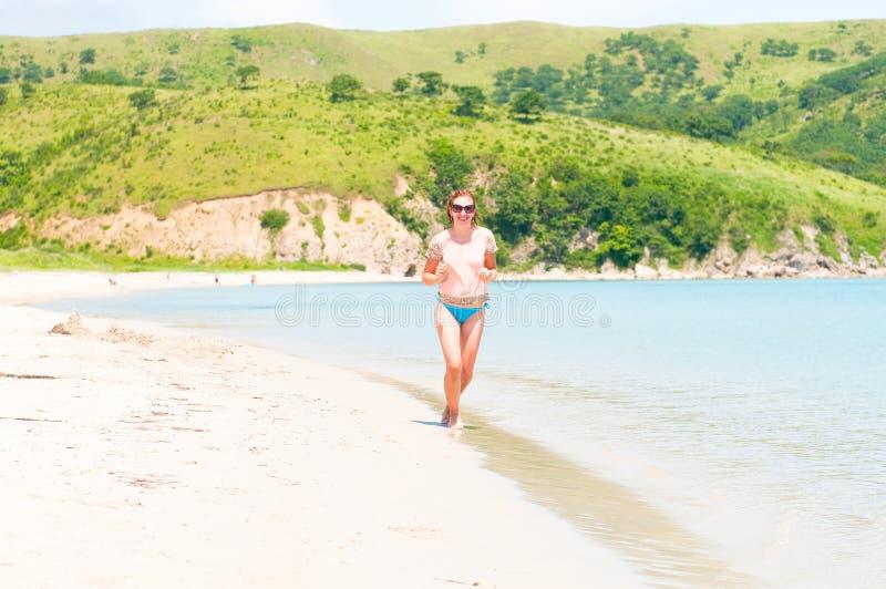 Happy girl running on the ocean beach royalty free stock photos