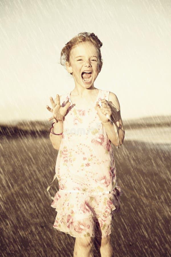 Happy girl running in rain