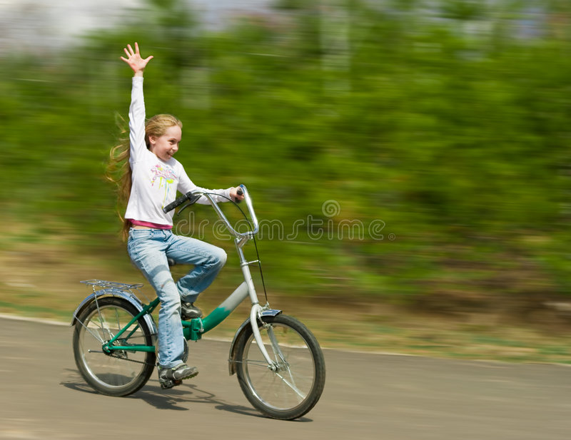 Happy girl rushes with bicycle with motion blur stock photo