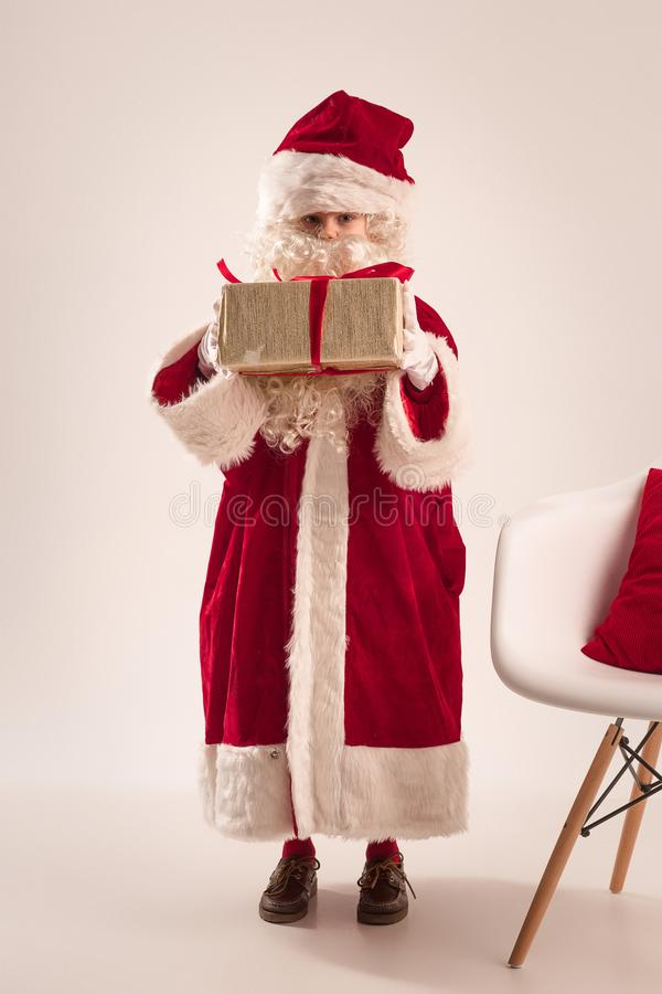 The happy girl in santa claus costume with gift box at studio stock photo