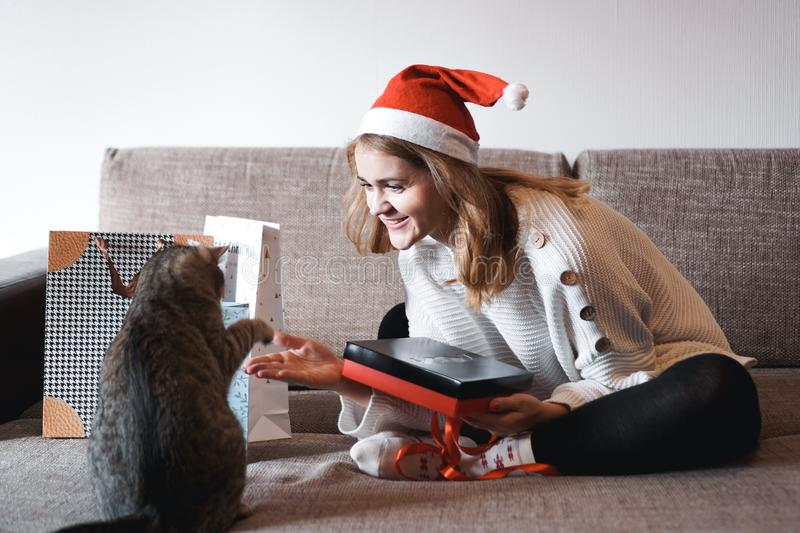 Happy girl in santa hat opening christmas gift box and playing with cat stock photo